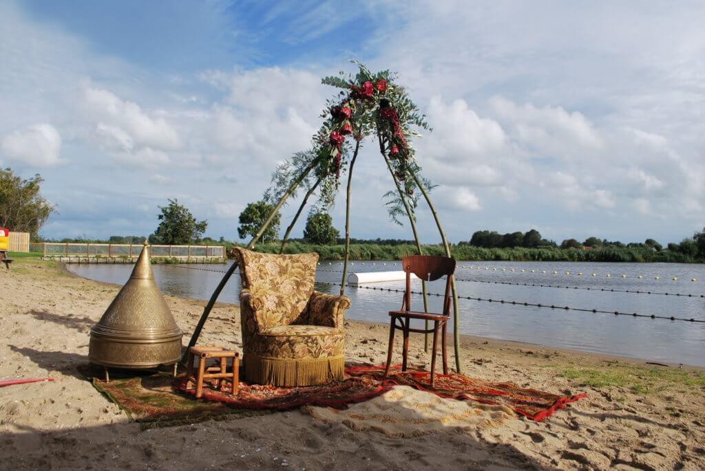 Ceremonie op strand met tipi bloemenkrans